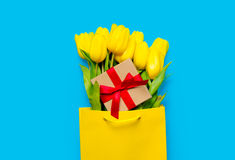 Bunch of yellow tulips and cute gift  in cool shopping bag on th Royalty Free Stock Image