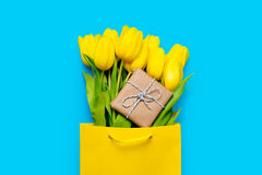 Bunch of yellow tulips and cute gift  in cool shopping bag on th Stock Photos