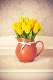 Bunch yellow tulips in jug on wooden table Stock Photo