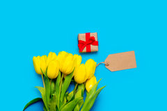 Bunch of yellow tulips, price tag and beautiful gift on the wond Royalty Free Stock Images