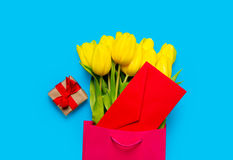 Bunch of yellow tulips and red envelope in cool shopping bag and Stock Photography