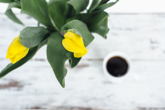 Bunch of yellow tulips on wooden table with cup of white tea Stock Image