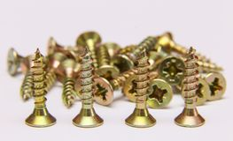 Bunch of yellow zinc coated philips flat head cross screws - fasteners. On a white background Stock Photos