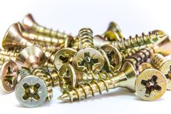 Bunch of yellow zinc coated philips flat head cross screws - fasteners. On a white background Royalty Free Stock Image