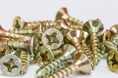 Bunch of yellow zinc coated philips flat head cross screws - fasteners. On a white background Royalty Free Stock Photos