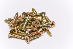 Bunch of yellow zinc coated philips flat head cross screws - fasteners. On a white background royalty free stock images