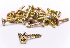 Bunch of yellow zinc coated philips flat head cross screws - fasteners. On a white background Royalty Free Stock Photo