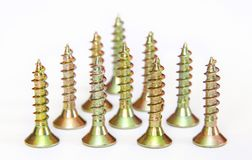 Bunch of yellow zinc coated philips flat head cross screws - fasteners. On a white background stock photo