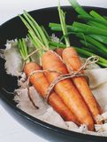 Bunch of young carrots with green tops on white wooden vintage table, healthy food on mock up background top view. Diet and vegetarian orange vegetable Stock Photos