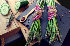 Bunches of asparagus with spices and cucumber Royalty Free Stock Image