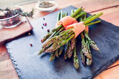 Bunches of asparagus wrapped in salmon with spices Stock Photos