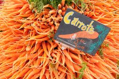Bunches of Carrots at a Farmers Market. Bunches of bright orange carrots at a Farmers Market completely fill the photo frame, along with a colorful hand-made Stock Images