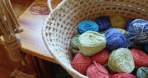 Bunches of different coloured woollen yarn kept in basket 4k