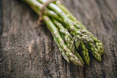 Bunches of fresh raw asparagus. On rustic wooden background Royalty Free Stock Photos