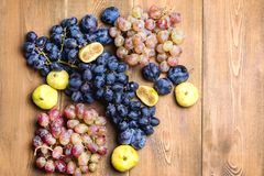 Bunches of fresh ripe grapes and figs on a wooden background Beautiful background with a branch of blue and red grapes. Figs Top v. Bunches of fresh ripe red Stock Photo