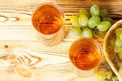 Bunches of fresh ripe green grapes in wicker basket on piece of sackcloth and two glasses with grape juice on a wooden textured ba stock photos