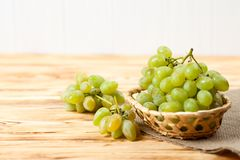 Bunches of fresh ripe green grapes in wicker basket on piece of sackcloth on a wooden textured backdrop. Beautiful background with royalty free stock photo