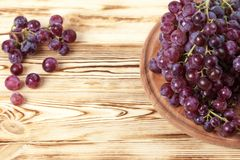 Bunches of fresh ripe pink grapes in wicker basket on piece of sackcloth on a wooden textured backdrop. Beautiful background with royalty free stock photos