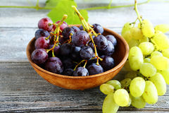 Bunches of grapes in bowl on wooden boards Stock Image