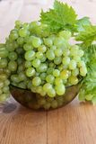 Bunches of green grapes in a Cup. Bunches of grapes in a bowl on the table stock photography