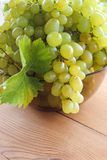 Bunches of green grapes in a Cup. Bunches of grapes in a bowl on the table stock photo