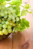 Bunches of green grapes in a Cup. Bunches of grapes in a bowl on the table royalty free stock photo