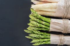 Bunches of green and white asparagus on a dark wooden background top view royalty free stock photo