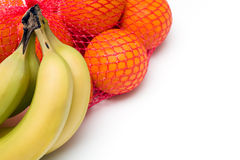 Bunches of Oranges and Bananas. Bunches of Oranges in netting, and Bananas, isolated on white Stock Image