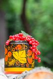 Bunches of ripe red currant in decorative wooden pot, painted in Khokhloma style. The currant is one of the most widespread berry shrubs of the Russian garden Stock Photos