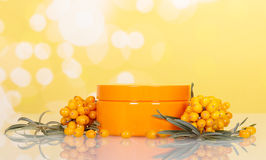 Bunches sea buckthorn and jar with cream on  abstract yellow. Stock Photos