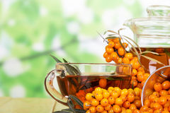 Bunches of sea buckthorn, a jug and  cup with  drink from her abstract green background. Stock Photo