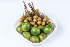 Bunchs of longan and oranges. In white basket  on white background Stock Photography