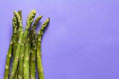 Buncj di asparago verde su fondo porpora con lo spazio della copia fotografie stock libere da diritti