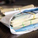 Bundel van Amerikaanse dollarbankbiljetten in witte envelop op houten lijst Secundair zwarte economieconcept Enveloplonen Omkoper royalty-vrije stock fotografie