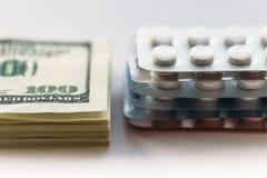 Bundel van geld en pak medicijntabletten of drugpillen, close-up Duur gezondheidszorgconcept royalty-vrije stock afbeeldingen