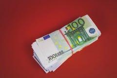bundel van geldrekeningen op een rode achtergrond royalty-vrije stock foto