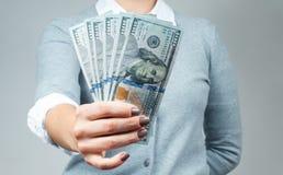 Bundel van rekeningen van honderd dollars in vrouwelijke handen royalty-vrije stock afbeeldingen
