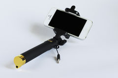 Bunden selfiepinne med en smartphone på en vit bakgrund Royaltyfri Foto