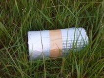 Bunden upp tejpad återvinningpåserulle på gräsgräsmattan utanför Arkivbild