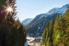 Bunderishka polyana, ski station, cable car lift, Bansko, Bulgaria, pine trees, sun between trunks Royalty Free Stock Images