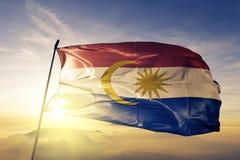 Bundesgebiet von Labuan des Malaysia-Flaggentextilstoffgewebes, das auf den Spitzensonnenaufgangnebelnebel wellenartig bewegt stockfoto