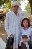 BUNDI,拉贾斯坦,印度- 2017年12月09日:一个老人的画象在白色摆在穿戴了与两个孩子和一只山羊在vill 图库摄影
