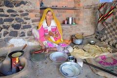 BUNDI,拉贾斯坦,印度- 2017年12月09日:准备薄煎饼平的面包的一个美丽的少妇的画象在庭院o里 免版税库存照片