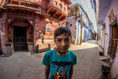 Bundi Indien - Februari 11, 2017: En pojke som ser kameran i en gata av Bundi, Rajasthan, Indien Förvriden sikt för fisköga royaltyfria foton