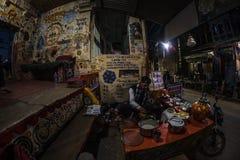 Bundi Indien - Februari 11, 2017: Man som maler kryddor för att göra indiern att mjölka te eller chai i en berömd gatamatstall i  royaltyfri fotografi