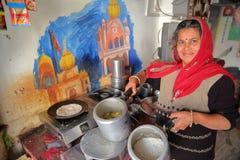 BUNDI, RAJASTHAN, INDIA - DECEMBER 10, 2017: Portret van een vrouw die in haar keuken een traditionele maaltijdthali voorstellen royalty-vrije stock afbeeldingen