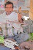 BUNDI, RAJASTHAN INDIA, GRUDZIEŃ, - 08, 2017: Portret sprzedawca trzyma tradycyjną parę waży przy jarzynowym rynkiem Obrazy Royalty Free