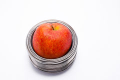 Bundit äpple: helt rött äpple i isolerade spolar av aluminum tråd Royaltyfria Bilder