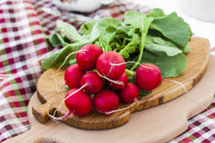 Bundle of  bright fresh organic radishes with leaves. In rustic style Stock Photo