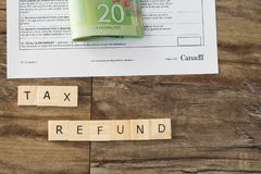 Tax refund spelled out in letters with Canadian Dollar cash in background. Bundle of cash to be paid out as a tax refund after taxes are filled stock photography